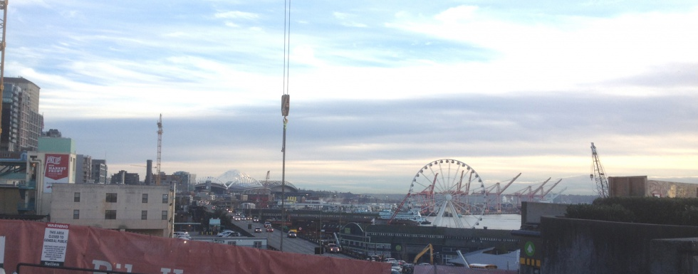 The harbor of Seattle with the Ferris wheel to the right and Mount Rainier far away to the left.
